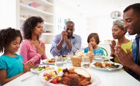 Family around dinner table offering Thanksgiving prayers