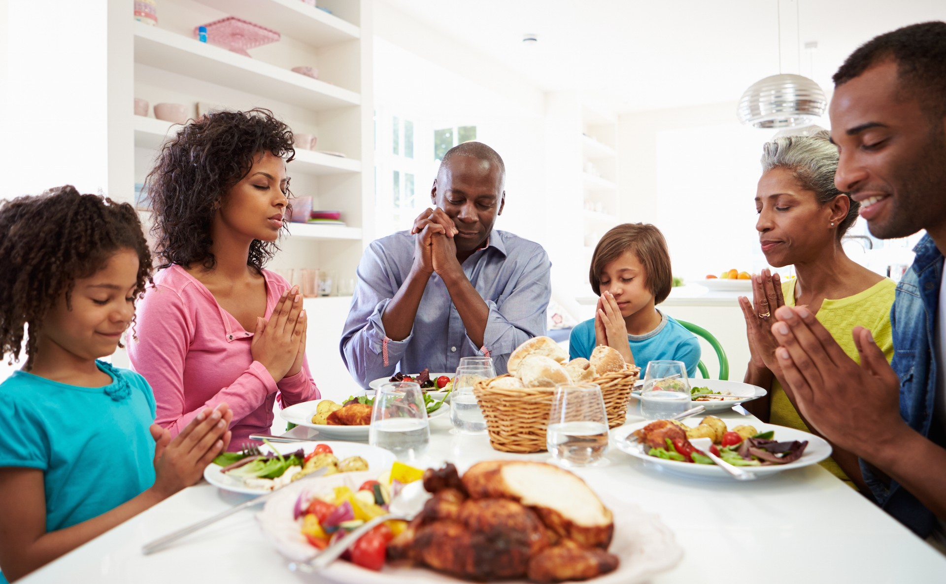 Family around dinner table offering Thanksgiving prayers