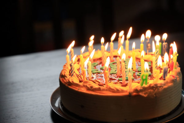 Chocolate birthday cake with candles lit