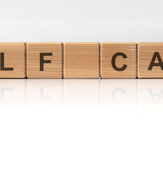 """Scrabble letters spelling """"self care"""" against a white background."""