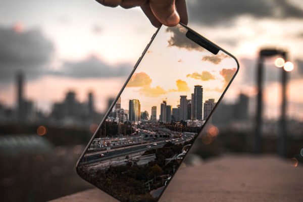 Person holding phone which is showing city-scape with city also visible in background.