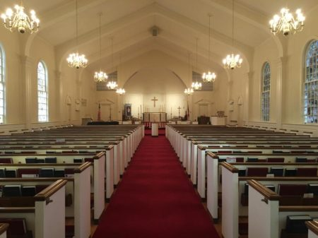 Church interior with wooden pews and red carpet.