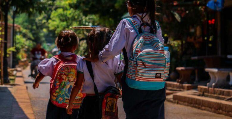 Backs of three children walking together wearing backpacks.
