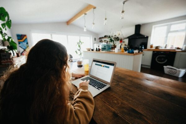 Girl with brown hair working on laptop at kitchen table.