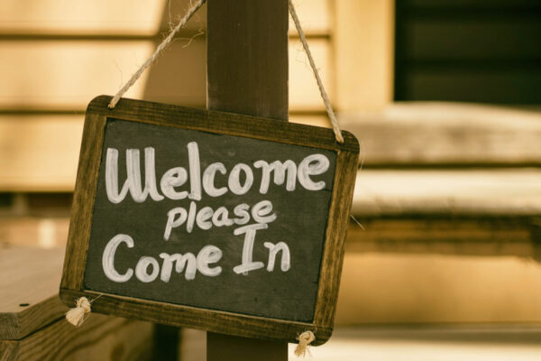 """Small chalkboard hanging from twine with white words, """"Welcome please come in."""""""