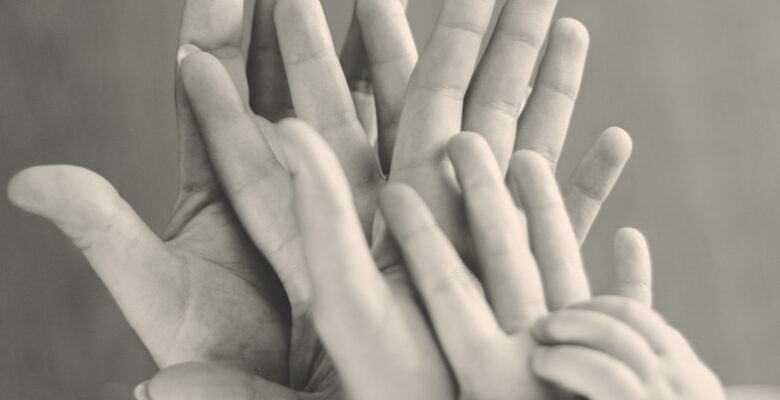 Black and white image of five hands stacked together.