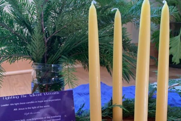 Wooden Advent wreath with beeswax candles, greenery in background, and prayer for lighting candles.