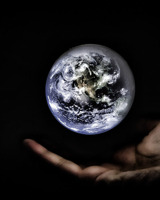Hand with globe floating above.