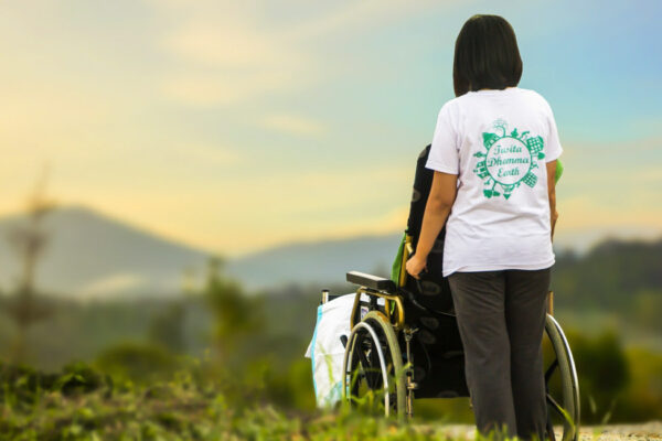 Woman in white shirt pushing wheelchair with mountain range in background.