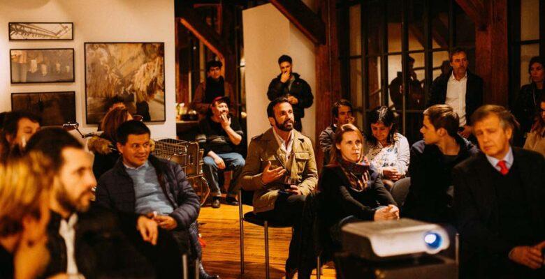 Group of people in dim lit room watching presentation.