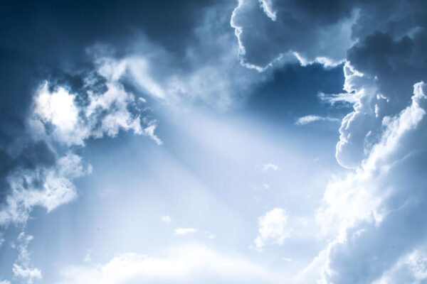 Blue sky, white clouds with light shining through.