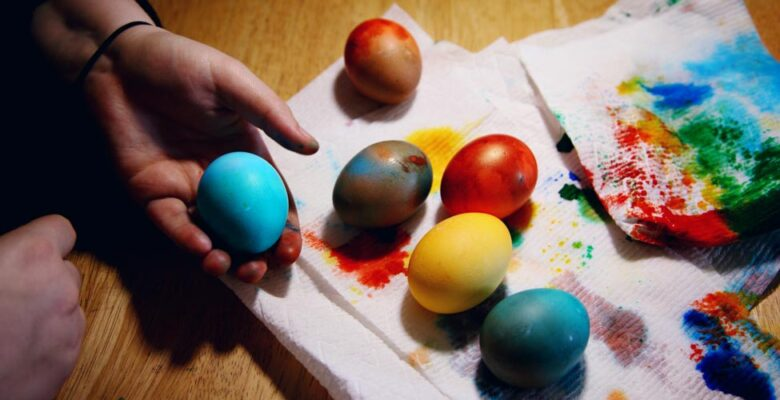 Egged dyed different colors on a paper towel stained with dye. One light blue egg is held in a hand.