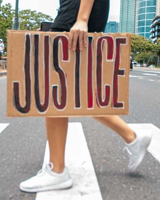"""Cardboard sign with word """"justice"""" painted in red and black. Sign in being carried across a cross walk by a white person."""