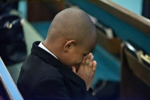 Young boy sitting in pew with hands folded in prayer.