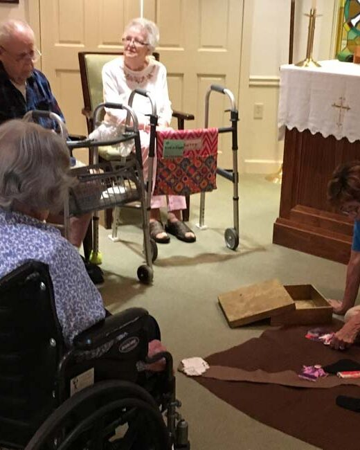 Older adults in chairs and wheelchairs watching woman on floor with Godly Play parable.